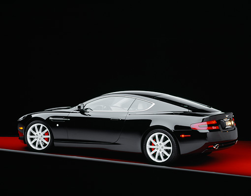 AUT 06 RK0068 05 © Kimball Stock 2005 Aston Martin DB9 Coupe Black 3/4 Rear View On Red Floor Gray Line Studio