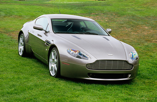 AUT 06 RK0072 03 © Kimball Stock 2006 Aston Martin DB7 Vantage Gray 3/4 Front View On Grass Aston Martin In Background