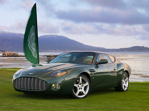 AUT 06 RK0098 01 © Kimball Stock 2003 Aston Martin DB7 Zagato Green 3/4 Front View On Grass By Flag Water Mountains