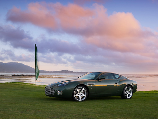 AUT 06 RK0100 01 © Kimball Stock 2003 Aston Martin DB7 Zagato Green 3/4 Front View On Grass By Flag Water Sky Mountains