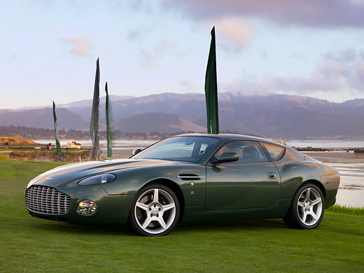 AUT 06 RK0103 01 © Kimball Stock 2003 Aston Martin DB7 Zagato Green 3/4 Front View On Grass By Flag Water Mountains