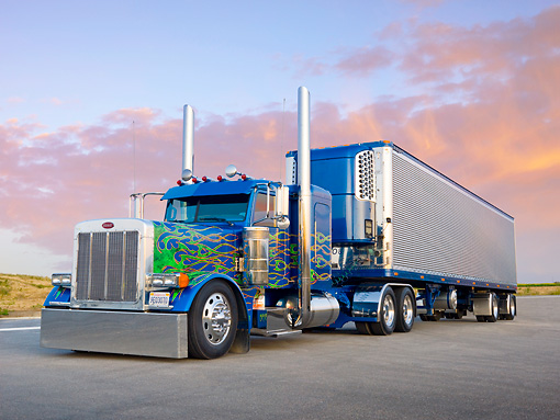 AUT 07 BK0001 01 © Kimball Stock 2007 Peterbilt 379 Big Rig Blue With Green Flames 3/4 Front View On Pavement By Sunset