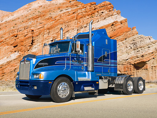AUT 07 RK0053 01 © Kimball Stock 1989 Kenworth T600 Big Rig Blue 3/4 Side View On Road By Red Rock