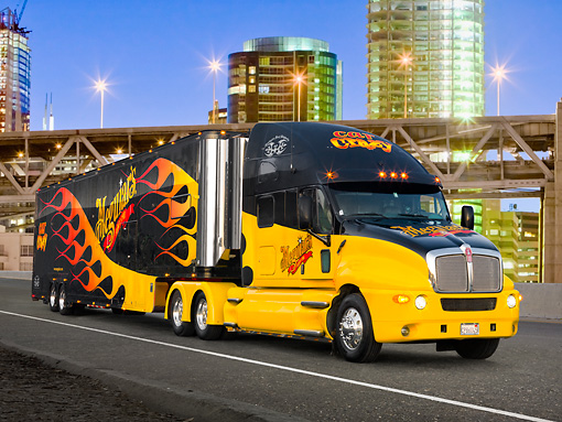 AUT 07 RK0054 01 © Kimball Stock 2005 Kenworth T2000 Big Rig Black With Flames 3/4 Front View On Road In City At Night