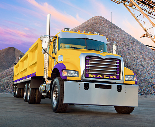 AUT 07 RK0179 01 © Kimball Stock Mack Big Rig Yellow And Purple 3/4 Front View On Pavement By Piles Of Gravel
