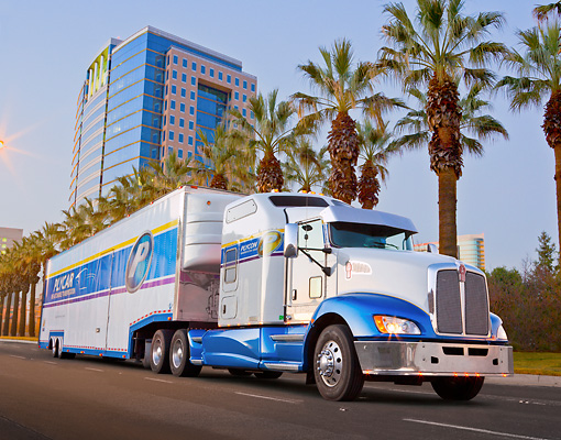 AUT 07 RK0185 01 © Kimball Stock 2012 Kenworth T660 White And Blue 3/4 Front View On Road By Palm Trees And Building