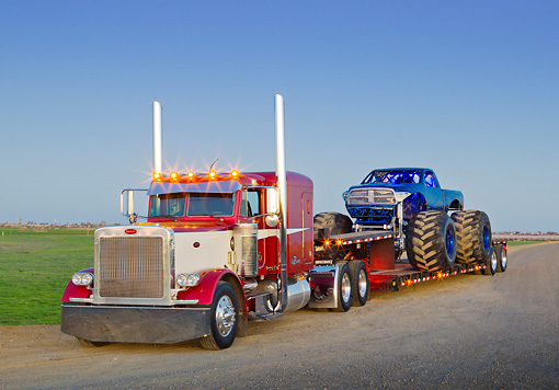 AUT 07 RK0192 01 © Kimball Stock 1999 Peterbilt 379 Red, White And Blue And 2011 Dodge Ram Monster Truck Black With Blue Flames On Dirt Road