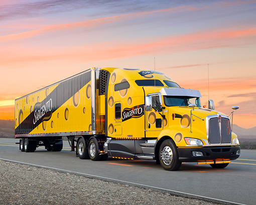 AUT 07 RK0257 01 © Kimball Stock 2010 Kenworth T660 With Trailer Yellow 3/4 Front View On Road At Sunset