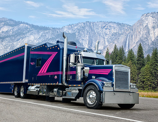 AUT 07 RK0271 01 © Kimball Stock 1996 Kenworth W900L Blue With Pink Stripe 3/4 Front View On Road By Mountains