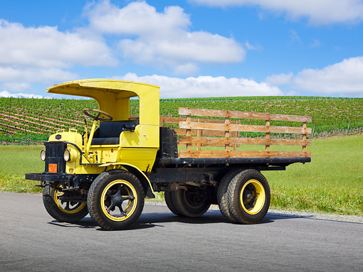 AUT 07 RK0374 01 © Kimball Stock 1922 Autocar 5 Ton Yellow 3/4 Front View On Pavement By Vineyard