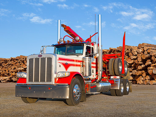 AUT 07 RK0398 01 © Kimball Stock 2010 Peterbilt 389 Red And White 3/4 Front View On Gravel By Logs