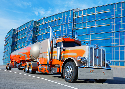 AUT 07 RK0399 01 © Kimball Stock 2012 Peterbilt 389 Tanker Orange And Gold 3/4 Front View On Pavement By Glass Building