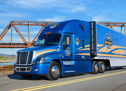 AUT 07 RK0407 01 © Kimball Stock 2014 Freightliner Cascadia Evolution Blue 3/4 Front View On Road By Bridge