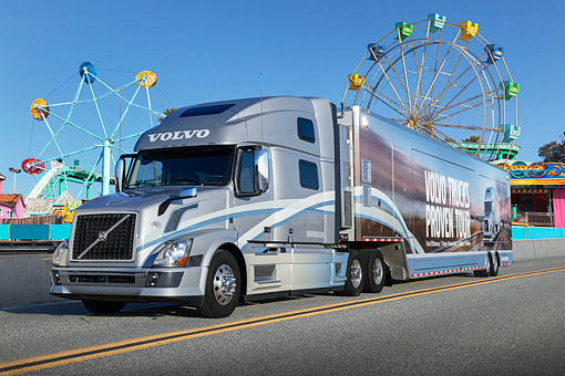AUT 07 RK0435 01 © Kimball Stock 2010 Volvo Semi Truck Silver 3/4 Front View On Road By Ferris Wheels