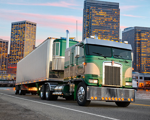 AUT 07 RK0442 01 © Kimball Stock 1986 Kenworth K100 Green And Mocha 3/4 Front View On Road By Skyscrapers At Dusk