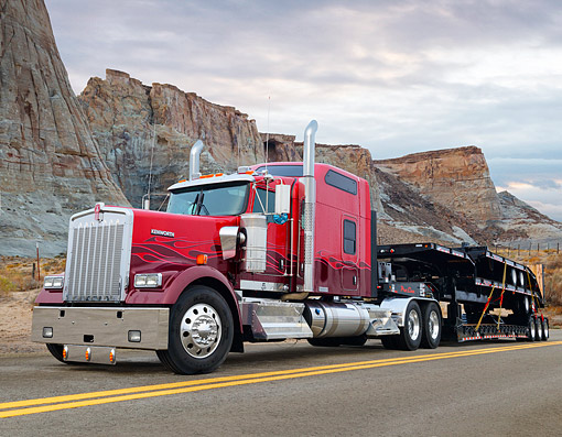 AUT 07 RK0498 01 © Kimball Stock 2014 Kenworth W900 Red With Low Boy Trailer 3/4 Front View Driving On Mountain Desert Road