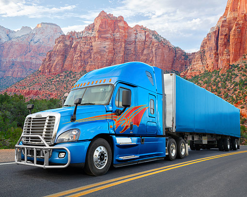 AUT 07 RK0509 01 © Kimball Stock 2015 Freightliner Cascadia Blue With Custom Graphics 3/4 Front View On Road In Desert