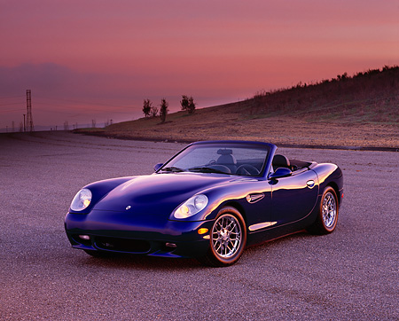 AUT 08 RK0014 06 © Kimball Stock 2000 Panoz Esperante Prototype Blue 3/4 Front View On Pavement Hills Purple And Pink Sky