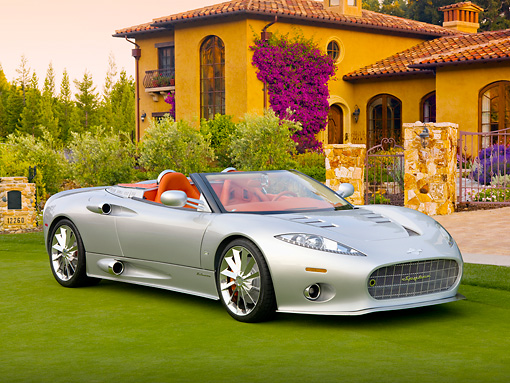 AUT 09 BK0018 01 © Kimball Stock Spyker C8 Aileron Spyder Silver 3/4 Front View On Grass By Building