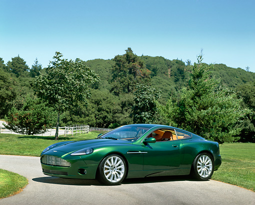 AUT 09 RK0199 02 © Kimball Stock Aston Martin Vantage Green Concept Car 3/4 Side View On Pavement By Grass And Trees Blue Sky