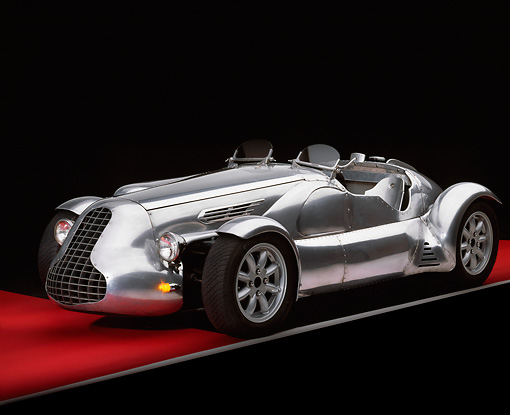 AUT 09 RK0427 05 © Kimball Stock Special Six Roadster Silver Front 3/4 View On Red Floor Gray Line Studio