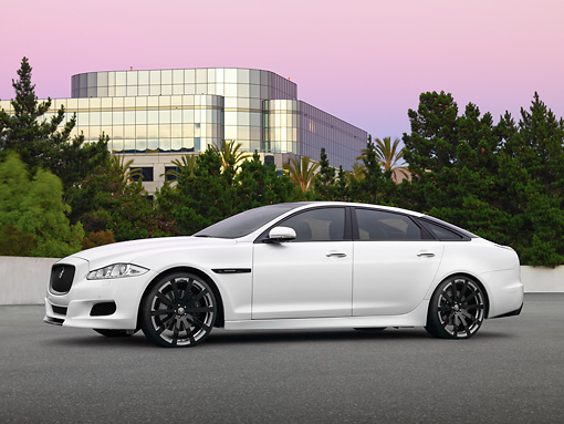 AUT 09 RK1215 01 © Kimball Stock Jaguar XJ 70 Concept White 3/4 Side View On Pavement By Building And Trees At Dusk