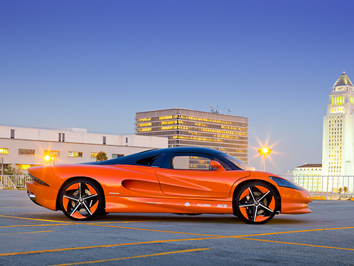 AUT 09 RK1230 01 © Kimball Stock 2011 Vision SZR Concept Orange Profile View On Pavement By Buildings At Dusk