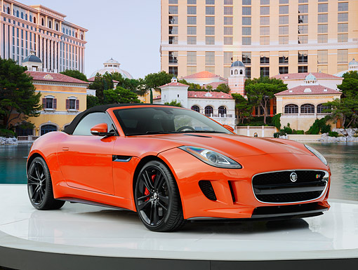 AUT 09 RK1306 01 © Kimball Stock Jaguar F-Type Convertible Concept Orange 3/4 Front View On Platform By Water And Buildings