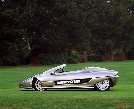 AUT 09 RK0029 01 © Kimball Stock 1992 Bertone Blitz Electric Car Profile On Grass By Trees
