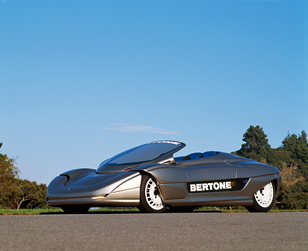 AUT 09 RK0032 02 © Kimball Stock 1992 Bertone Blitz Electric Car 3/4 Side View On Pavement By Trees And Blue Sky