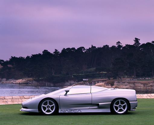 AUT 09 RK0187 02 © Kimball Stock BMW Ital Design Nazca Concept Car Silver Profile View On Grass Gray Sky By Water