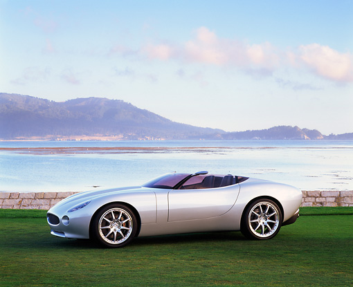 AUT 09 RK0380 03 © Kimball Stock Jaguar F-Type Concept Roadster Silver 3/4 Side View On Grass By Water Mountains