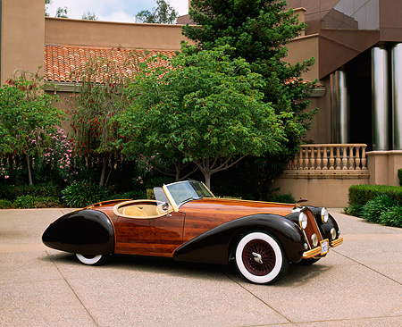 AUT 09 RK0400 02 © Kimball Stock The Dolphin Wooden Roadster Front 3/4 View On Pavement By Building And Trees