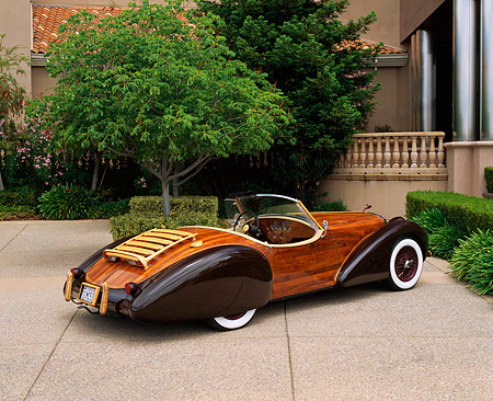 AUT 09 RK0402 04 © Kimball Stock The Dolphin Wooden Roadster Rear 3/4 View On Pavement By Building And Trees