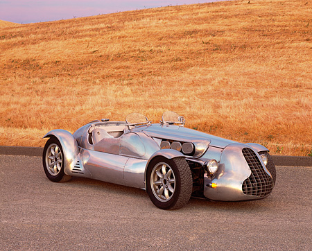 AUT 09 RK0407 04 © Kimball Stock Special Six Roadster Silver Side 3/4 View On Pavement By Dry Grass Hill