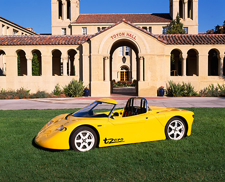 AUT 09 RK0446 05 © Kimball Stock AC Propulsion tZero Electric Sports Car Prototype Yellow Side 3/4 View On Grass By Building
