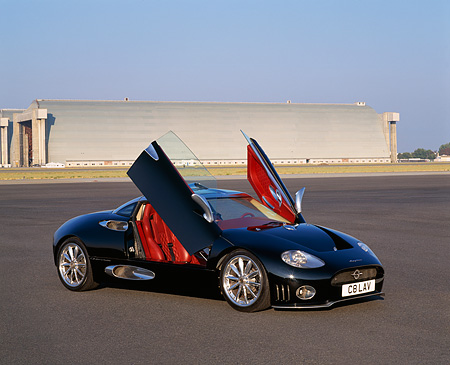 AUT 09 RK0456 02 © Kimball Stock Spyker C8 Laviolette Coupe Black 3/4 Front View Doors Open On Pavement By Hangar