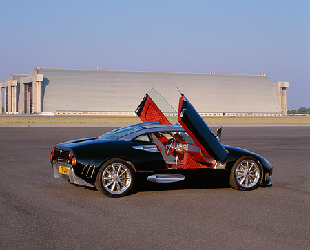 AUT 09 RK0460 01 © Kimball Stock Spyker C8 Laviolette Coupe Black 3/4 Rear View Doors Open On Pavement By Hangar