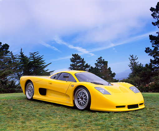 AUT 09 RK0505 02 © Kimball Stock 2002 Mosler MT900S Photon Yellow 3/4 Side View On Grass Trees Blue Sky