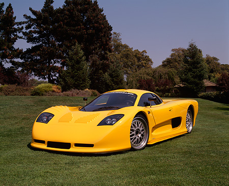 AUT 09 RK0509 02 © Kimball Stock 2002 Mosler MT900S Photon Yellow 3/4 Front View On Grass Trees Blue Sky