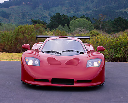 AUT 09 RK0661 03 © Kimball Stock 2003 Mosler MT900S Prototype Rosa Barchetta Head On View On Pavement By Shrubs Hills