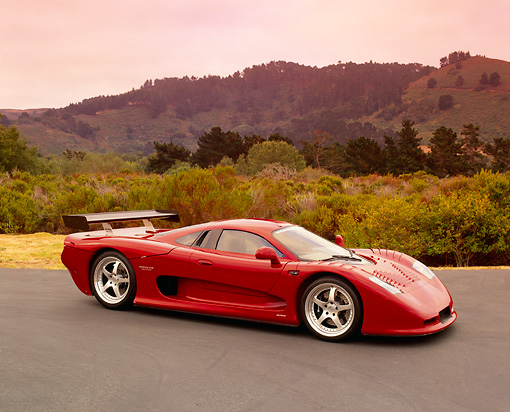 AUT 09 RK0664 01 © Kimball Stock 2003 Mosler MT900S Prototype Rosa Barchetta 3/4 Front View On Pavement Bushes Background