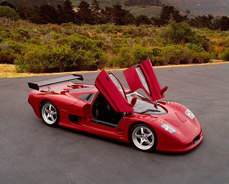 AUT 09 RK0665 03 © Kimball Stock 2003 Mosler MT900S Prototype Rosa Barchetta 3/4 Front View Door Open On Pavement By Bushes