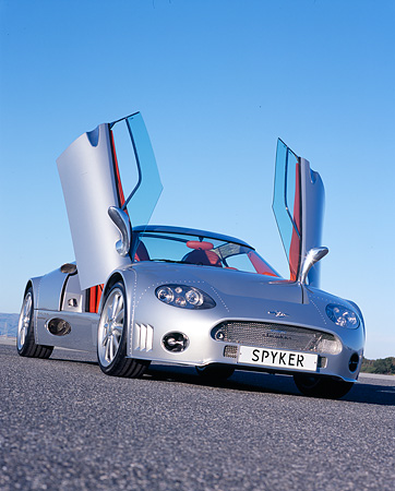 AUT 09 RK0844 02 © Kimball Stock 2006 Spyker C8 Double 12 S Silver Slanted Low 3/4 Front View Doors Open On Pavement Blue Sky