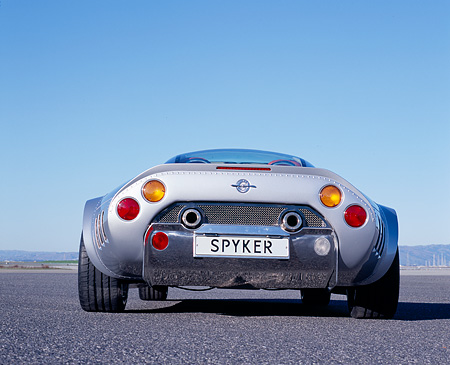 AUT 09 RK0851 01 © Kimball Stock 2006 Spyker C8 Double 12 S Silver Low Rear View On Pavement Blue Sky