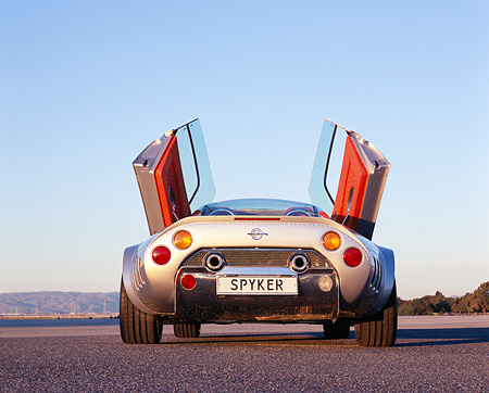 AUT 09 RK0853 01 © Kimball Stock 2006 Spyker C8 Double 12 S Silver Low Rear View Doors Open On Pavement Blue Sky