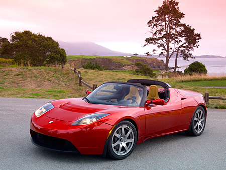 AUT 09 RK0882 01 © Kimball Stock Tesla Roadster Electric Car Red 3/4 Front View On Pavement By Grass And Trees