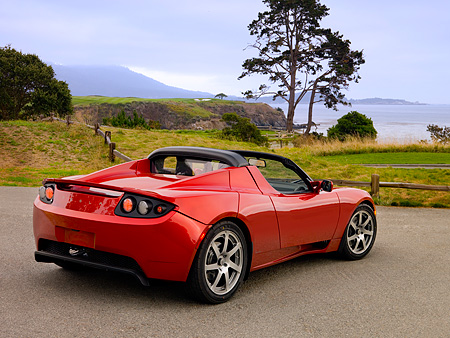 AUT 09 RK0883 01 © Kimball Stock Tesla Roadster Electric Car Red 3/4 Rear View On Pavement By Grass And Trees