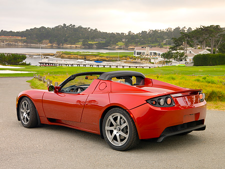 AUT 09 RK0884 01 © Kimball Stock Tesla Roadster Electric Car Red 3/4 Rear View On Pavement By Grass And Trees