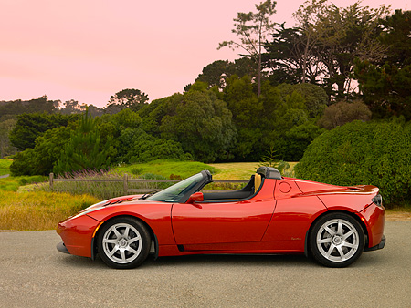 AUT 09 RK0885 01 © Kimball Stock Tesla Roadster Electric Car Red Profile View On Pavement By Grass And Trees